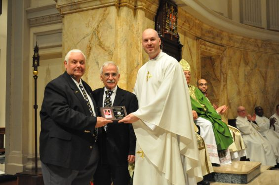 Father Peter Purpura accepts a check from the Knights for the cathedral's bells.