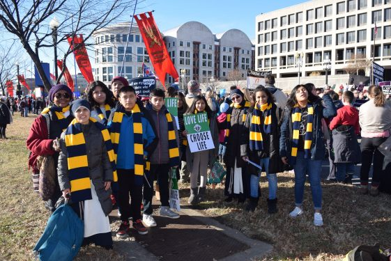 Young people and religious sisters from St. Joseph Co-Cathedral, Prospect Heights, get set to take part in the march up Constitution Ave. while wearing festive scarves that identified Brooklyn and Queens marchers.
