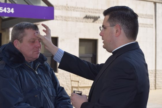 Seminarian Michael Falce distributes ashes to a visitor at NYU Langone Medical Center in Brooklyn.