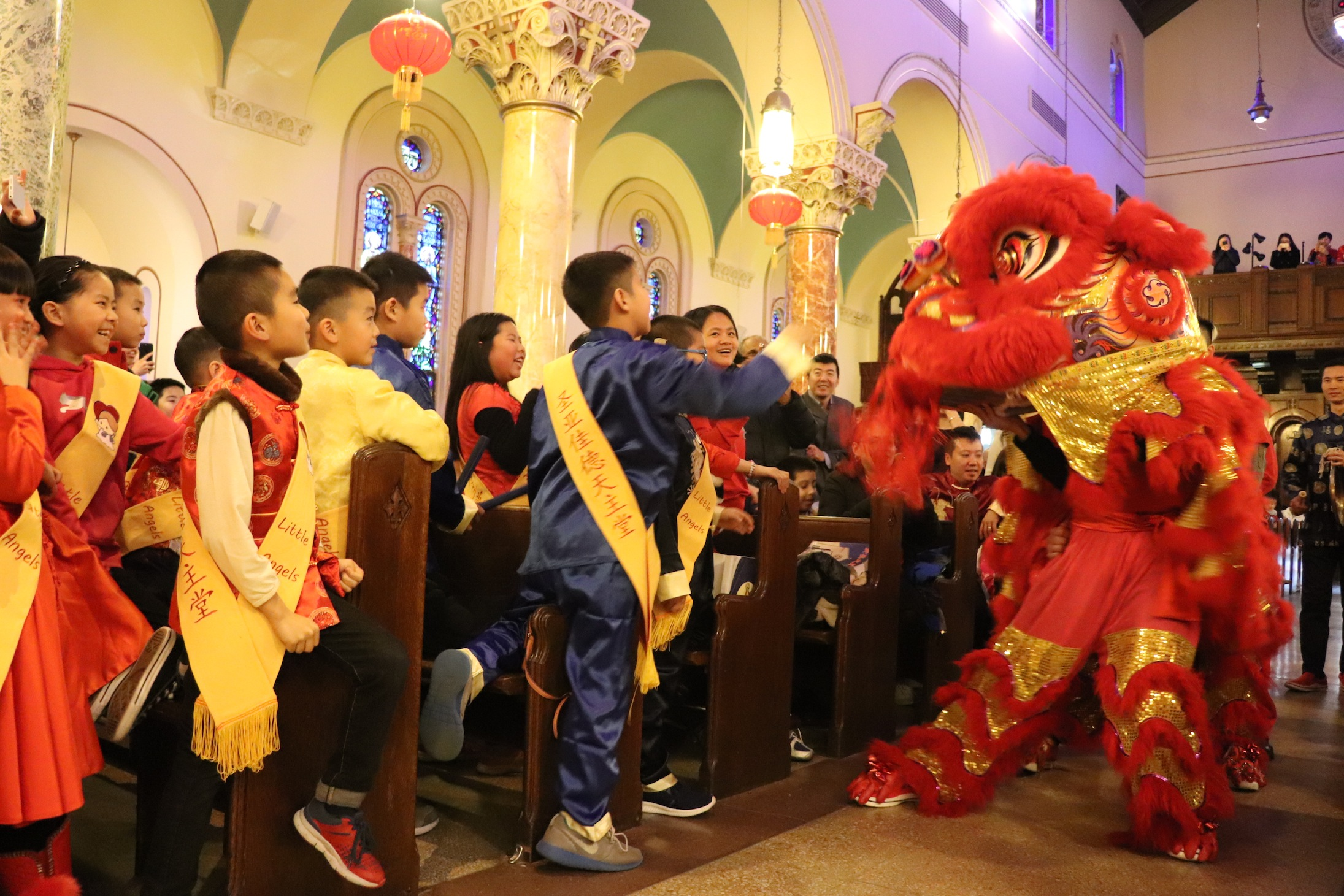a festive dragon followed to the glee of the children the traditional red dragon marched to the beat of drums engaging the congregation