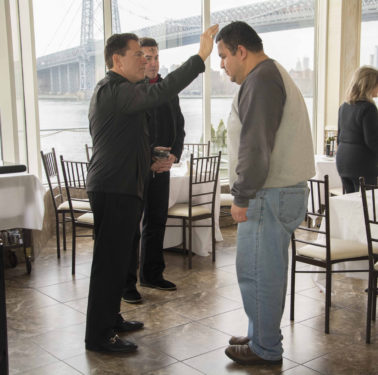 Msgr. Jamie Gigantiello, pastor of Our Lady of Mount Carmel parish, Williamsburg, distributed ashes to the staff at Giando's-on-the-Water, a popular restaurant near his church.
