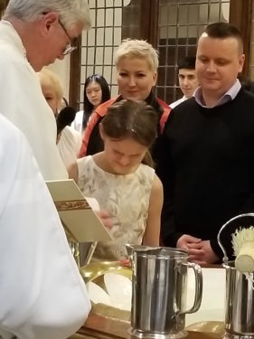 Parishioners at Our Lady of Mercy Church in Forest Hills, welcomed Lena into the Church, as Msgr. John McGuirl, pastor, baptized her at the Easter Vigil. Lena's godparents flew in from Poland for this special occasion, and stood beside her at the baptismal font. Photo AnnaMarie Prono