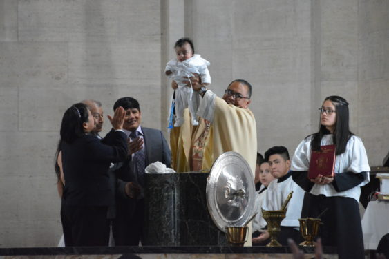 Father Jorge Ortiz, administrator of St. Brigid's parish, Bushwick, raises a child for the community to see after he baptized her at Easter Vigil at the church. (Photo Jorge Dominguez)