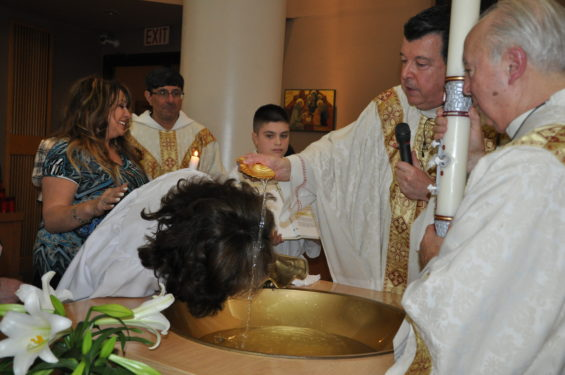 Msgr. Joseph Grimaldi, pastor of St. Bernard Church, Mill Basin, performs a  baptism during the Easter Vigil liturgy at the church. He is assisted by Deacon Frank D'Accordo. Photo Rita Damato