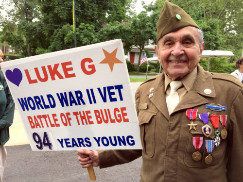World War II veteran Luke Gasparre, 94, proudly displays the sign he carries in the annual Little Neck-Douglaston Memorial Day Parade. A resident of Astoria, Gasparre attends St. Joseph Church and works as an usher at Citi Field.