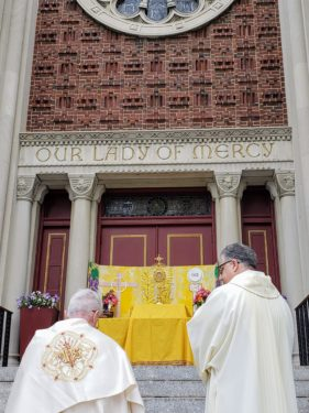 The Feast of the Body of Christ was observed with eucharistic processions in Brooklyn and Queens. In Forest Hills, Msgr. John McGuirl, pastor of Our Lady of Mercy, and Deacon Dean Dobbins pause before the Blessed Sacrament on the church steps .Photo AnnaMarie Prono