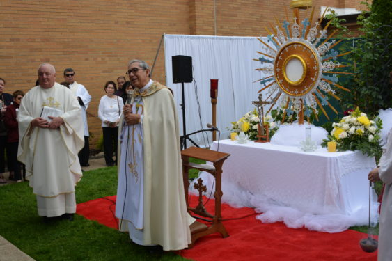 Bishop Octavio Cisneros observed the Feast of Corpus Christi with the Woodside parish named for this solemnity. The bishop stands alongside Father Patrick West, pastor of Corpus Christi, as he speaks to the crowds, right, in front of a makeshift altar.