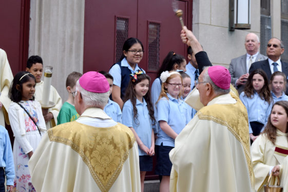 Bishop Nicholas DiMarzio blesses the newly renovated St. Kevin Catholic Academy, Flushing. Looking on are students and Bishop Raymond Chappetto, pastor, at left.