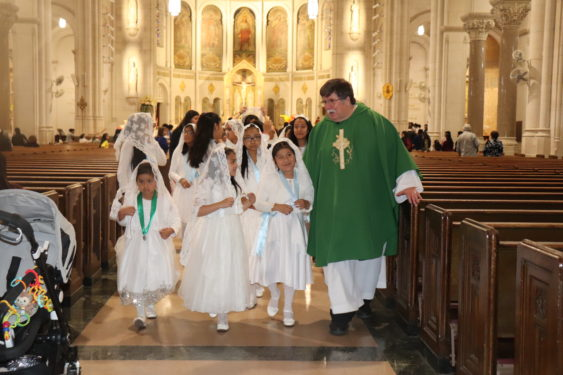 Father John McKenna, C.Ss.R, processes out with the Daughters of Mary during the closing hymn, sang by the children's choir.