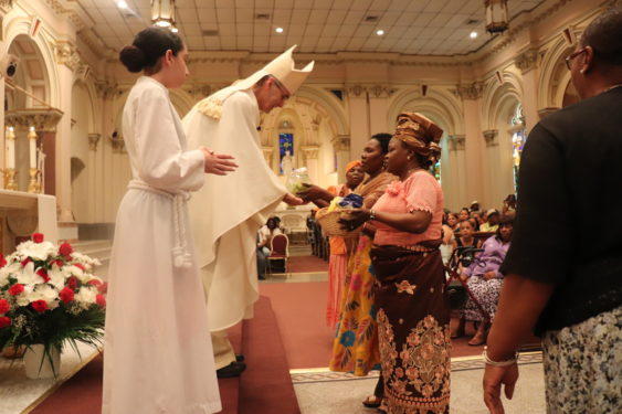 Auxiliary Bishop Paul Sanchez accepts the gifts in the offertory procession at the 150th anniversary Mass of St. John the Baptist parish in Bedford-Stuyvesant.