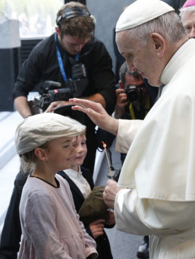 Pope Francis holds a candle as he greets children while visiting the Chapel of the Apparitions at the Knock Shrine in Knock, Ireland, Aug. 26. (CNS photo/Paul Haring)