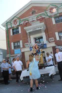 Teresa Curcio tosses rose petals before a statue of Our Lady of the Snow to celebrate the saint's feast day and the 130th anniversary of the Society of St. Mary of the Snow in Williamsburg. Curcio is the president of the ladies auxiliary.