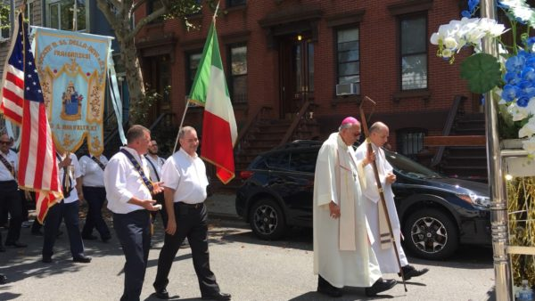 Bishop Nicholas DiMarzio celebrated the Society of St. Mary of the Snow's 130th anniversary by joining members in a street procession. Front row, from left, Vinny Raymond, society president; Deacon Jaime Varela, the bishop's master of ceremonies; Bishop DiMarzio and Father Thomas Vassalotti, pastor, Divine Mercy parish, Williamsburg.