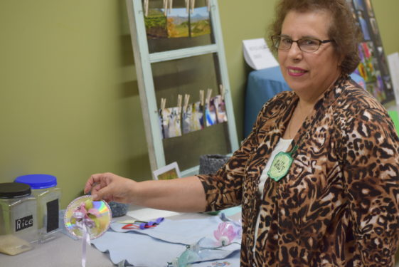 Sally Thomas presented her collection of recycled materials used to create new household items. She holds a CD that she turned into a pencil case.