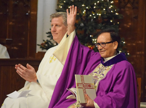 Father Jesus Cuadros, pastor emeritus, above, right, raises his hand as he is acknowledged during Mass. Sitting beside him is Father Mark Matthias, parish administrator.