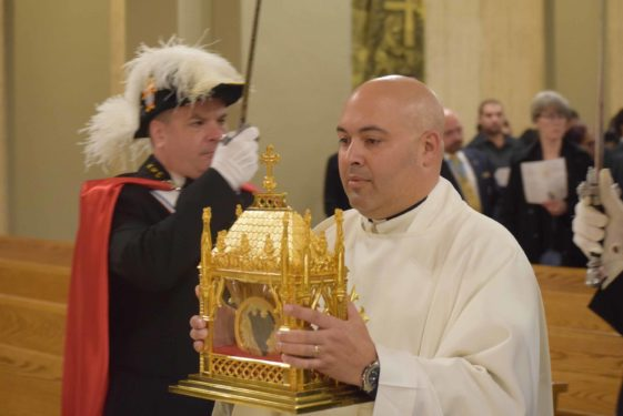 Father Michael Gelfant escorts the relic to the altar.