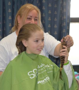 Madison Taravella Beadle, a fourth grade student at St. Mel's was the first young student brave enough to step onto the stage, she examines the locks she just donated to St. Baldrick's Conquer Kid's Cancer.