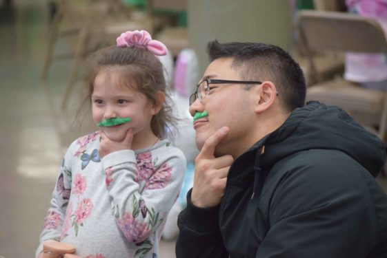 Father Jun Hee Lee, paroichial vicar at St. Mel's parish, shares a green moustache moment with a young supporter.