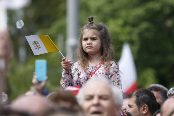 A child holds a Vatican flag as people wait for Pope Francis.