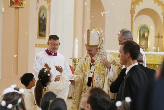 Flower petals fall as Pope Francis concludes Mass.