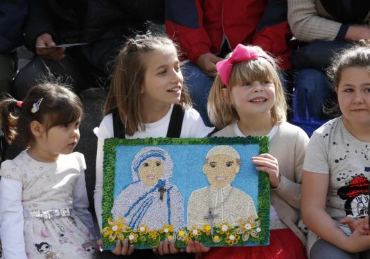 Children hold a gift showing St. Teresa of Kolkata and Pope Francis before the pope's visit to the Mother Teresa Memorial in Skopje, North Macedonia, May 7.