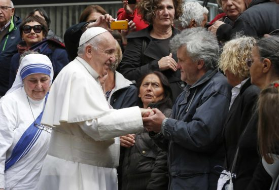 Pope Francis greets people as he visits the Mother Teresa Memorial for a meeting with religious leaders and the poor in Skopje.