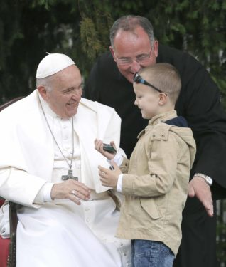 Pope Francis greets a child as attends an ecumenical and interreligious meeting with young people at the pastoral center.
