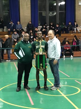 Knights senior point guard Tyler Chapman, center, was named tournament MVP. He's pictured with St. Thomas Aquinas pastor Father Dwayne Davis, left, and tournament director Guy DeFonzo, right. (Photo courtesy St. Thomas Aquinas Sports Association)